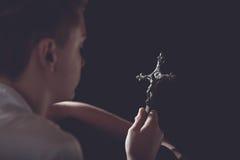 Adolescente contemplativo que lleva a cabo la cruz adornada Fotografía de archivo libre de regalías