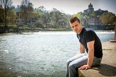 Adolescente contemplativo que se sienta al lado del río Imágenes de archivo libres de regalías