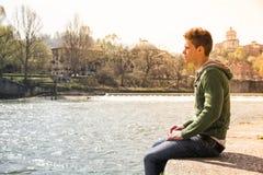 Adolescente contemplativo que se sienta al lado del río Foto de archivo