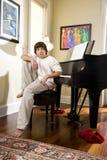 Adolescente contemplativo que se sienta en banco del piano Imagen de archivo libre de regalías