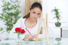 Adolescente contemplativo sentado en la tabla que sostiene el lápiz Fotografía de archivo