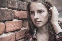 Adolescente contra una pared de ladrillo Imagenes de archivo