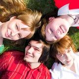 Adolescente cuatro puesto en hierba Foto de archivo