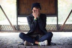 Adolescente cubrió su cara, mirando a escondidas a través de sus fingeres en la calle Fotografía de archivo libre de regalías