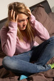 Adolescente déprimée s'asseyant dans la chambre à coucher à la maison Photo stock