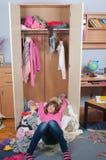Adolescente désordonnée se trouvant sur la pile des vêtements Images libres de droits