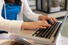 Adolescente da colheita que usa o portátil na biblioteca fotografia de stock royalty free