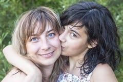 Adolescente da filha que beija sua família nova da mãe fora imagens de stock