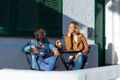 Adolescente da mãe e da filha que senta-se no terraço verde da mobília na cidade costeira europeia típica de Barcelona, na Espanh imagem de stock royalty free