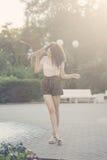 Adolescente da menina com cabelo encaracolado e skate foto de stock