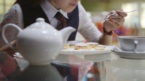 Adolescente da menina em uma farda da escola que senta-se em uma tabela no bar de escola que come bolos e que bebe o chá, close-u vídeos de arquivo