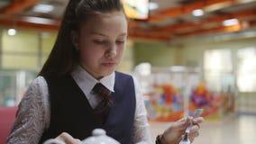 Adolescente da menina em uma farda da escola que senta-se em uma tabela no bar de escola que come bolos e que bebe o ch?, close-u vídeos de arquivo