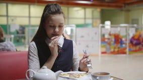 Adolescente da menina em uma farda da escola que senta-se em uma tabela no bar de escola que come bolos e que bebe o ch? filme