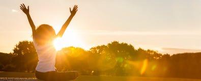 Adolescente da menina da jovem mulher que senta-se em Hay Bale Celebrating Sunset fotografia de stock