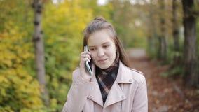 Adolescente da menina que anda no parque e que fala em um telefone celular, smartphone Tempo do outono, folhas e fresco amarelos filme