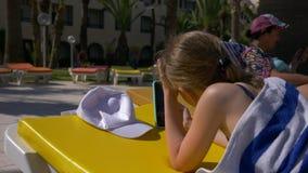 Adolescente da menina que encontra-se na espreguiçadeira perto da piscina e que usa o telefone celular filme