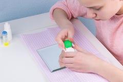 Adolescente da menina que guarda um recipiente com as lentes para a correção da visão, close-up Imagem de Stock
