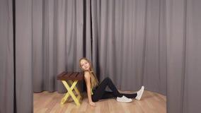 Adolescente da menina que levanta na sessão de foto da forma no estúdio no fundo cinzento video estoque