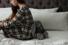 Adolescente da virada com o brinquedo que senta-se na cama imagem de stock royalty free
