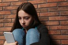 Adolescente da virada com o smartphone que senta-se na parede imagens de stock