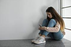 Adolescente da virada com o smartphone que senta-se no assoalho perto da parede foto de stock royalty free