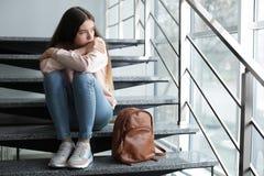 Adolescente da virada com a trouxa que senta-se em escadas dentro imagens de stock