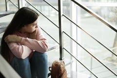 Adolescente da virada com a trouxa que senta-se em escadas dentro fotografia de stock royalty free