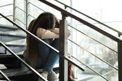 Adolescente da virada com a trouxa que senta-se em escadas dentro imagem de stock royalty free