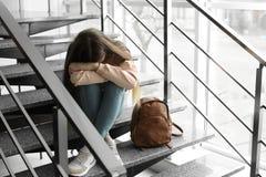 Adolescente da virada com a trouxa que senta-se em escadas dentro foto de stock