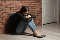 Adolescente da virada com a trouxa que senta-se no assoalho imagem de stock