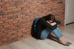 Adolescente da virada com a trouxa que senta-se no assoalho perto da parede imagens de stock royalty free