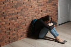 Adolescente da virada com a trouxa que senta-se no assoalho perto da parede fotos de stock