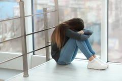 Adolescente da virada que senta-se na janela imagem de stock