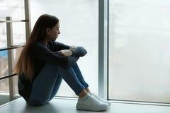 Adolescente da virada que senta-se na janela dentro foto de stock royalty free