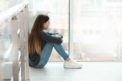 Adolescente da virada que senta-se na janela dentro fotografia de stock