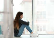 Adolescente da virada que senta-se na janela Espaço para o texto fotografia de stock