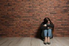 Adolescente da virada que senta-se no assoalho perto da parede foto de stock