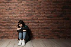 Adolescente da virada que senta-se no assoalho perto da parede imagens de stock