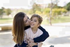 Adolescente dando un beso a su hermana más joven Imagen de archivo libre de regalías