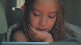 Adolescente dans le lit jouant un comprimé dans l'Internet social dans la lumière foncée Fermez-vous de peu de vidéo de observati banque de vidéos