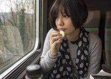 Adolescente de Amerasian que come una galleta en un tren Imagen de archivo