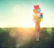 Adolescente de beauté sur le champ d'été avec les ballons à air colorés images stock