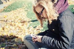 Adolescente de Bllond en los vidrios que se sientan en parque otoñal Imagen de archivo libre de regalías