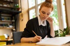 Adolescente de cabelo vermelho bonito que estuda na tabela fotografia de stock