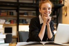 Adolescente de cabelo vermelho de sorriso que usa o portátil foto de stock royalty free