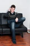 Adolescente de Causual que se sienta en un sofá que habla en su teléfono celular Imagenes de archivo