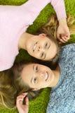 Adolescente de dos hermanas que miente en la alfombra Imagen de archivo