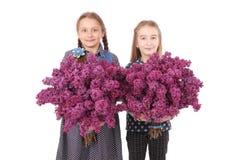Adolescente de dos muchachas que se coloca con la lila en manos Fotos de archivo