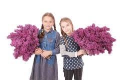 Adolescente de dos muchachas que se coloca con la lila en manos Imagenes de archivo