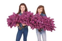 Adolescente de dos muchachas que se coloca con la lila en manos Fotos de archivo libres de regalías